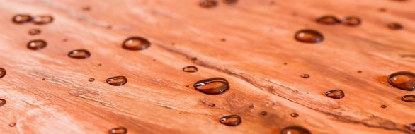 Water beads up on beautiful freshly sealed cedar wood decking after a morning rainstorm